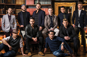 The Ten Tenors huddled in group image. Some standing, leaning on floor or siting.