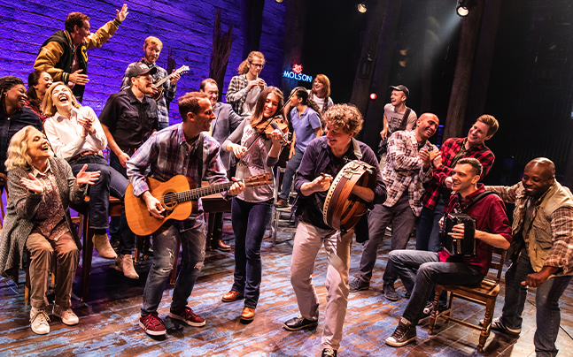 Cast of Come From Away on stage singing and playing instruments.