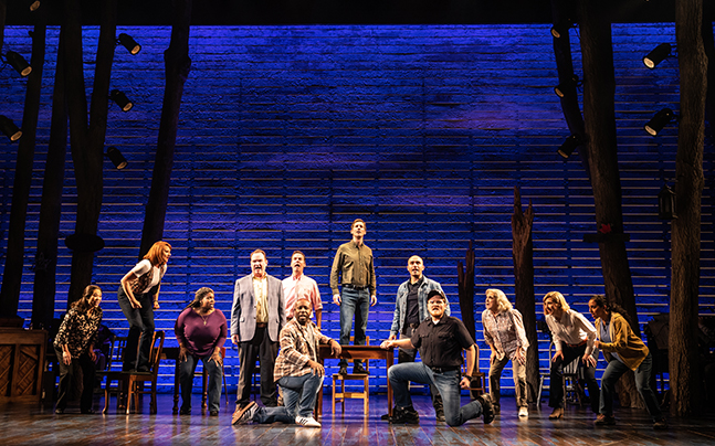 Cast of Come From Away on stage singing in a line some standing, kneeling.