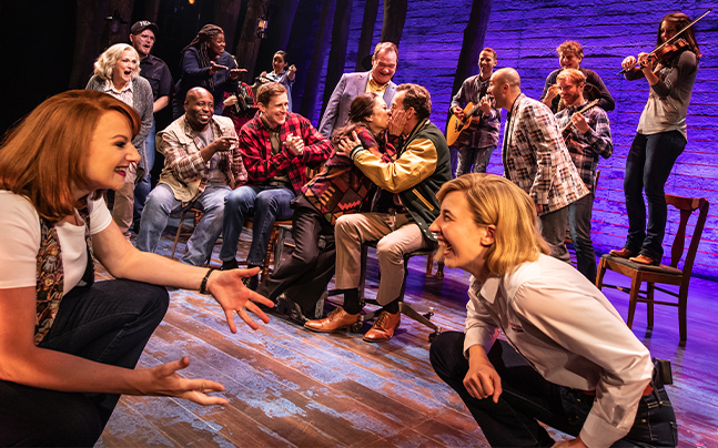 Cast of Come From Away on stage watching a couple kiss. Laughing and playing instruments.