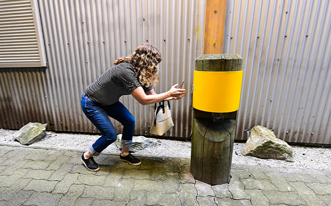 women crouches to read QR code on phone.