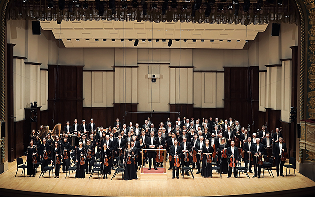 Full orchestra of Detroit Symphony Orchestra in hall with instruments