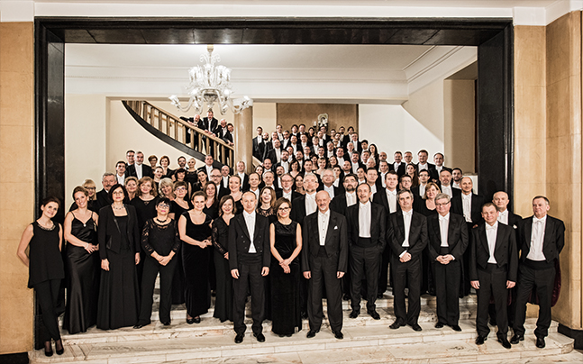 Full Warsaw Orchestra standing in hall in concert attire.