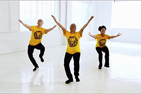 3 People in Lion King t-shirts dancing with outstretched arms