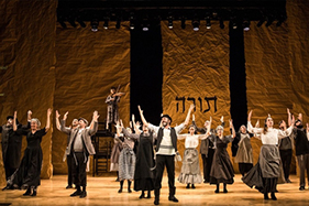 Fiddler cast members standing with outstretched arms