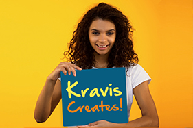 Girl holding sign smiling Kravis Creates!