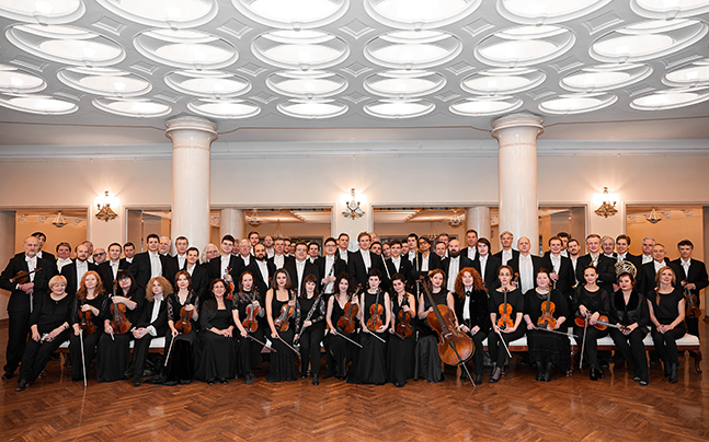 Full room of Russia National Symphony members with instruments.