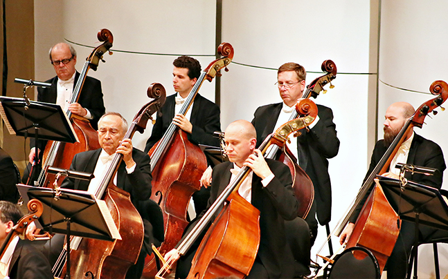 Russian National Orchestra members playing on string instruments.
