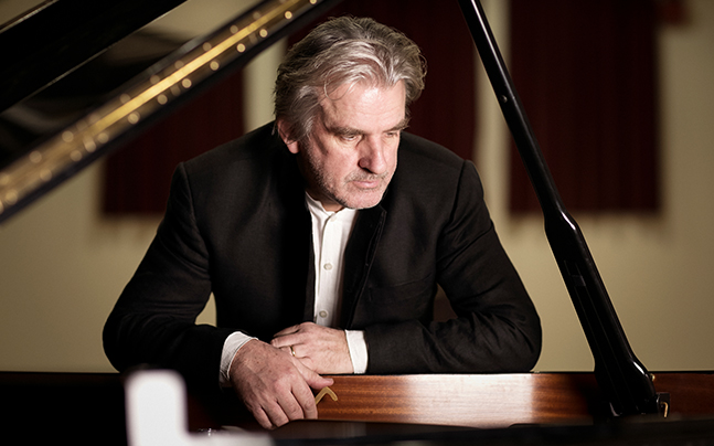 Barry Douglas looking down at open piano.