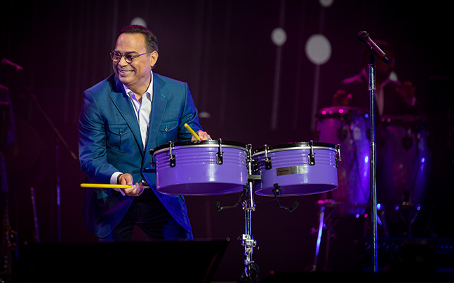 Gilberto on stage playing drums.