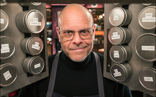 Alton Brown looking inside the cabinet smiling
