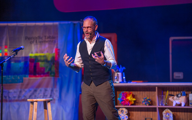 Alton Brown talking to audience on stage.