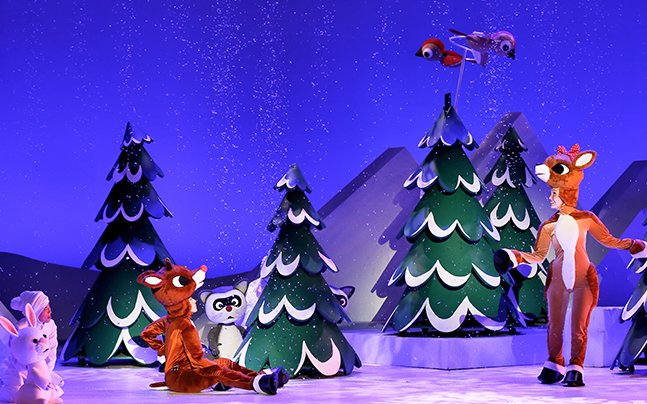 2 people in reindeer suits playing under the snow on the stage