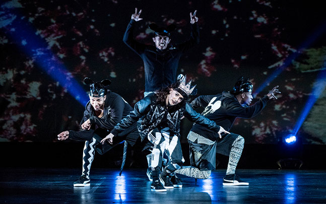 men and woman in black and white suits dancing on stage.