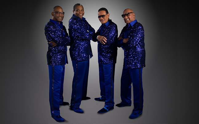 Temptations band members pose in blue suits.