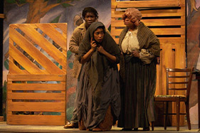 Three actors portraying slaves grouped together on stage