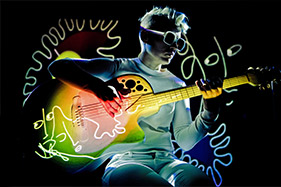 Woman dressed in white holding multi colored electric guitar