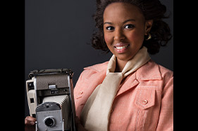 Annie Easley holding camera and smiling.