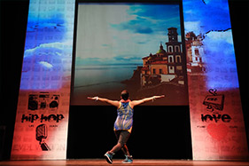 Dancer with arms outstretched facing large picture of Cuba