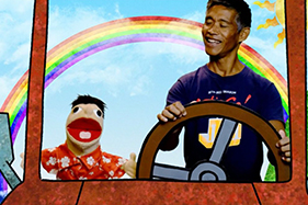 man and puppet driving imaginary car